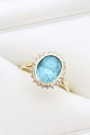 Gold ring with blue topaz and diamonds in jewel box