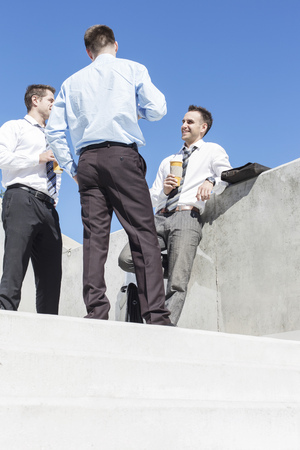 Poland, Warsaw, Businessmen standing on stairs, chatting