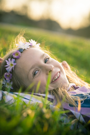Portrait of smiling little girl lying on meadow wearing flowers LANG_EVOIMAGES