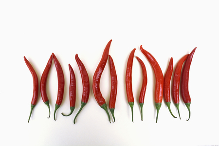 Row of red peppers in front of white background