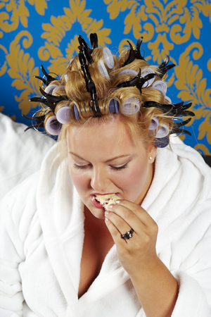 Portrait of woman with curlers and white bathrobe having breakfast in bed