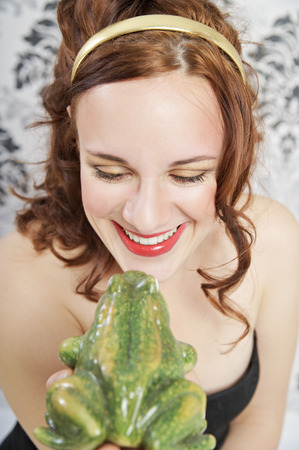 Portrait of smiling young woman kissing frog