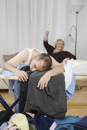 Exhausted man at ironing board with woman in background LANG_EVOIMAGES