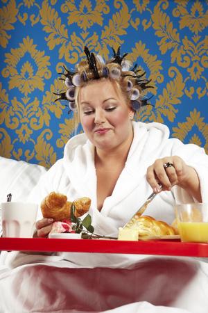 Mujer con rulos y bata blanca desayunando en la cama