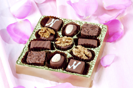Different nougat pralines in chocolate box on pink ground