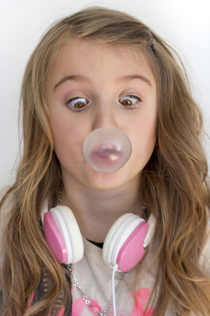 Girl with headphones peering at chewing gum bubble