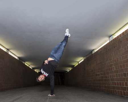 Young breakdancer performing a handstand in underpass