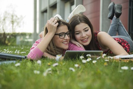 Two young women using digital tablet in meadow LANG_EVOIMAGES