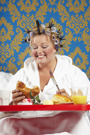 Woman with curlers and white bathrobe having breakfast in bed