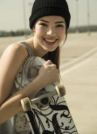 Portrait of smiling young woman with skateboard