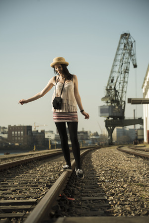 Young woman with old camera balancing on rail