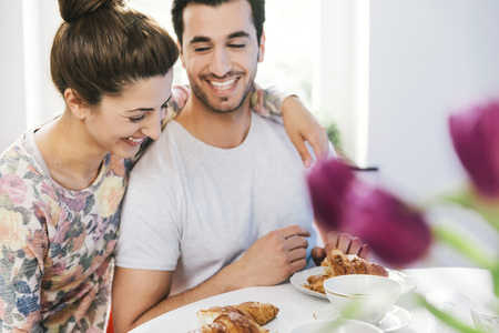 Laughing young couple at breakfast table