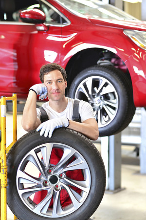 Car mechanic in a workshop changing tire LANG_EVOIMAGES