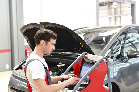 Car mechanic in a workshop using modern diagnostic equipment