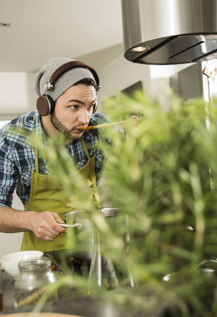 Young man with headphones cooking in kitchen at home LANG_EVOIMAGES