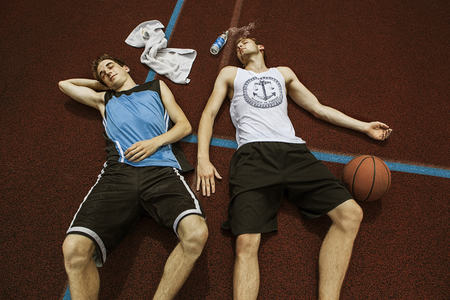 Portrait of two young basketball players relaxing on basketball ground