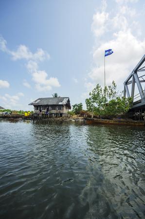 Indonesia, Riau Islands, Bintan Island, Fishing village, Fishing hut and flag LANG_EVOIMAGES