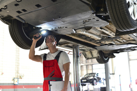 Car mechanic in a workshop checking underbody of a car LANG_EVOIMAGES