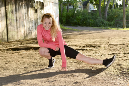 Young woman doing stretching exercise on sand LANG_EVOIMAGES