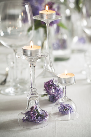 Table decoration with tea candles, glasses and lilac, Syringa