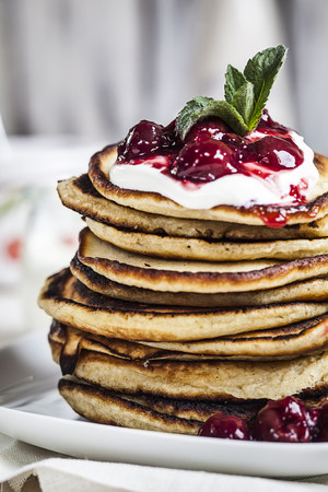 Stack of American pancakes with cherry sauce and greek yogurt, close-up