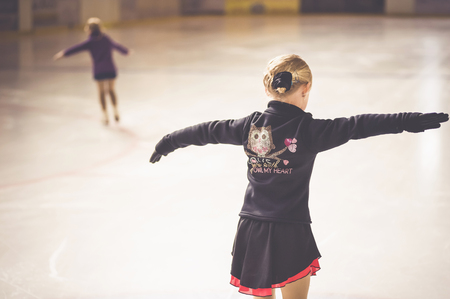 Two young female figure skaters on ice rink at competition