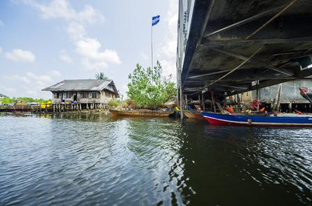 Indonesia, Riau Islands, Bintan Island, Fishing village, Bridge, Fishing hut and flag