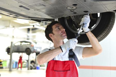 Car mechanic in a workshop working at car LANG_EVOIMAGES