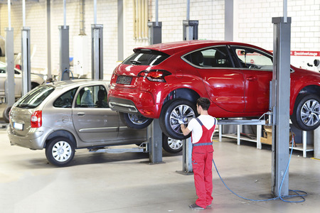 Car mechanic in a workshop changing tires