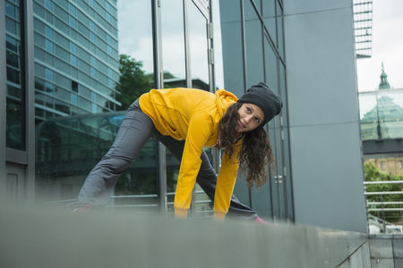 Young woman wearing yellow tracksuit top making stretching exercises