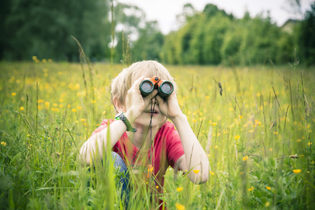 Little boy sitting on meadow watching something with binocular LANG_EVOIMAGES