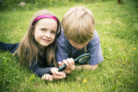 Brother and sister lying on meadow watching flower with magnifying glass LANG_EVOIMAGES
