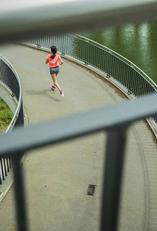 Young woman jogging on a bridge, back view LANG_EVOIMAGES