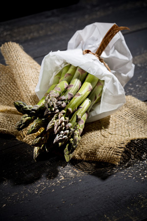 Bunch of green asparagus in white paper bag on jute and dark wood