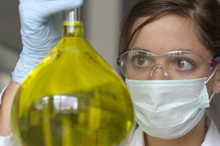 Portrait of female chemist holding Erlenmeyer flask with yellow liquid LANG_EVOIMAGES