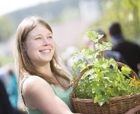 Portrait of smiling young woman holding basket with plants LANG_EVOIMAGES