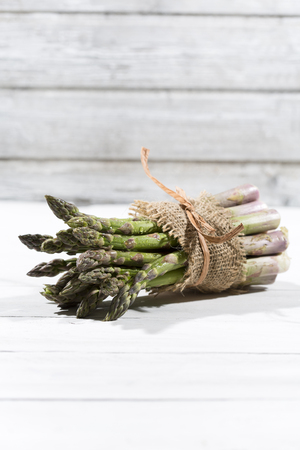 Bunch of green asparagus in front of white wood