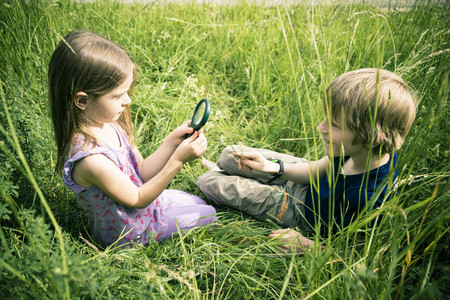 Brother and sister sitting on meadow playing with magnifying glass