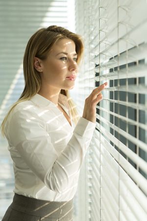 Businesswoman looking through blinds LANG_EVOIMAGES