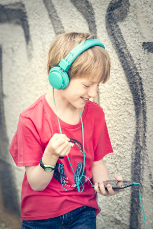 Portrait of happy boy with smartphone and headphones in front of facade