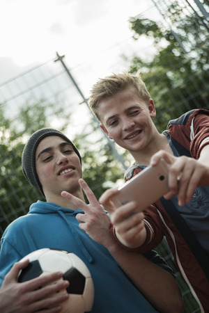 Two friends with soccer ball taking selfie