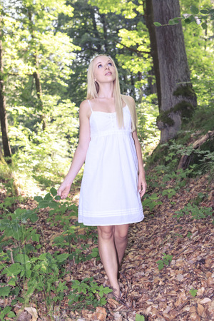 Portrait of a young woman wearing white dress standing in the forest LANG_EVOIMAGES