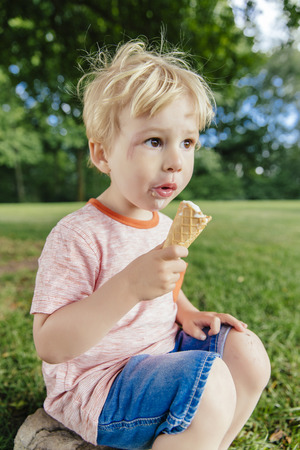 Germany, North Rhine-Westphalia, Bonn, Blonde male toddler eating icecream