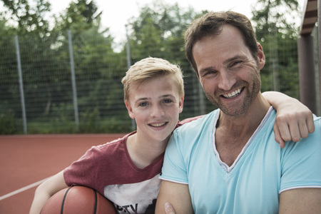 Germany, Mannheim, Father and son playing basket ball LANG_EVOIMAGES