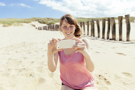 Portrait of woman photographing with her smartphone on the beach LANG_EVOIMAGES