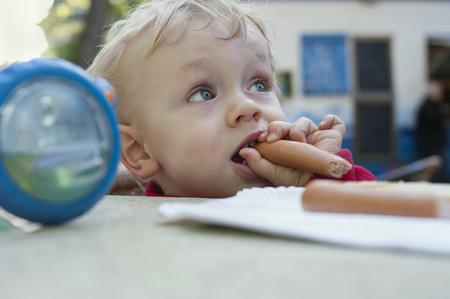 Baby boy eating a sausage LANG_EVOIMAGES