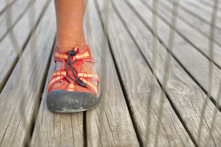 Foot with trekking sandal behind a fence on a boardwalk