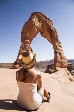 USA, Utah, woman sitting in front of Delicate Arch at Arches National Park, back view