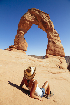 USA, Utah, woman relaxing in front of Delicate Arch at Arches National Park, back view LANG_EVOIMAGES
