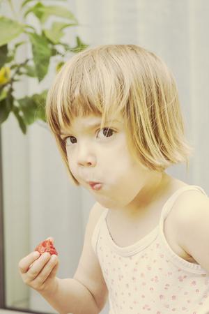 Portrait of little girl eating strawberry LANG_EVOIMAGES
